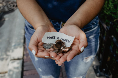 Hands holding spare change with a note that says make a change.