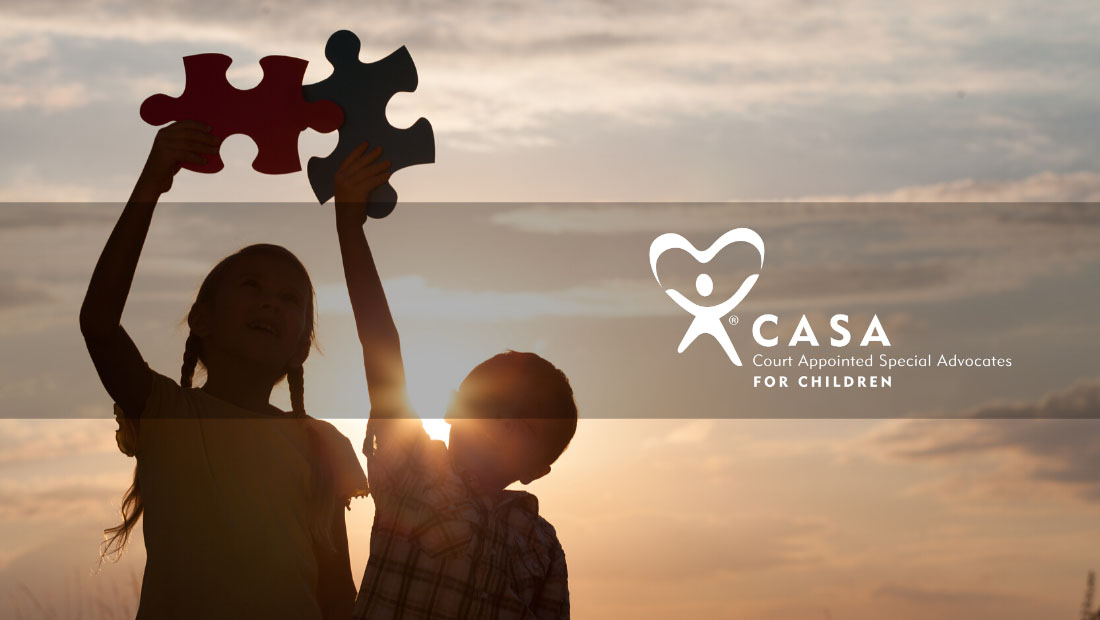 Female and male child silhouetted in the sunset holding up giant puzzle pieces.