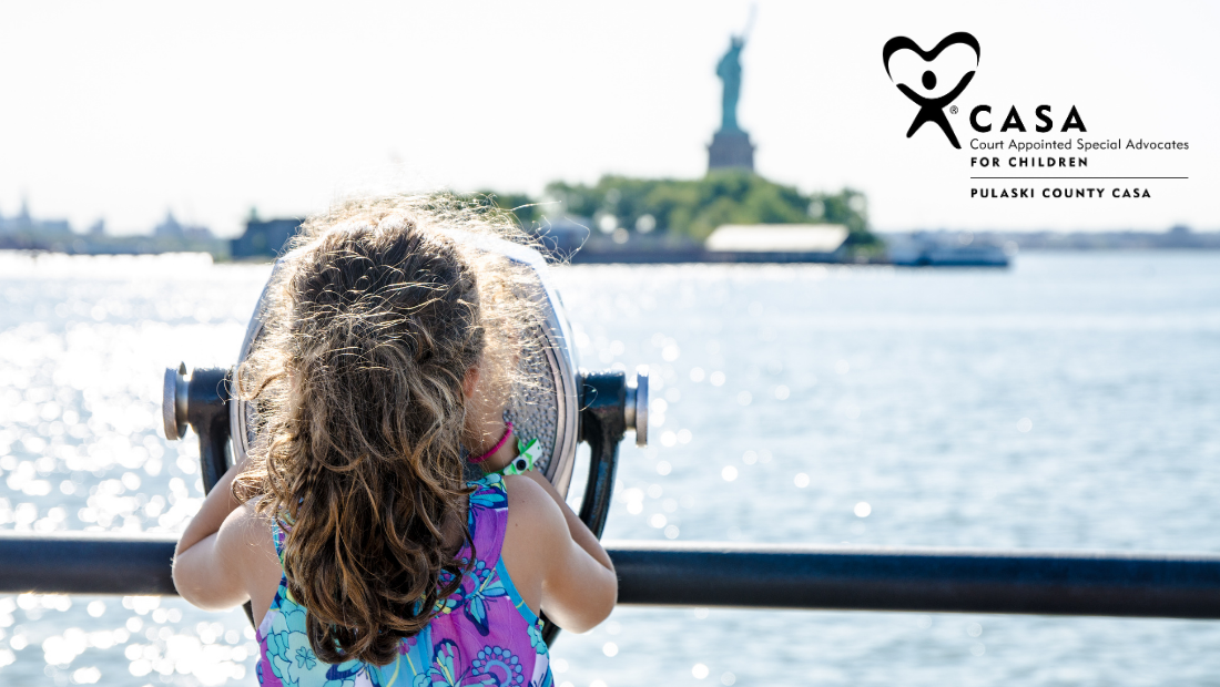 Young girl looking across the water at the Statue of Liberty