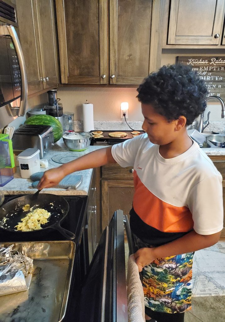 Boy cooking eggs.
